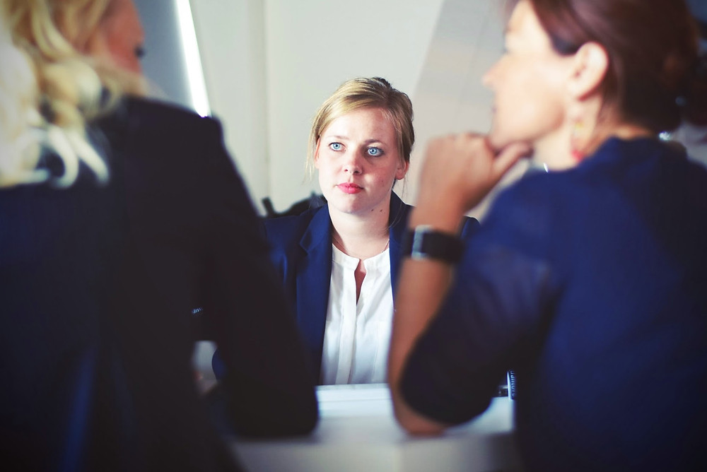 businesswoman staring intently as two other women talk during a meeting