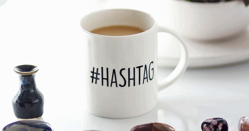 A white  coffee cup with word hashtag on it