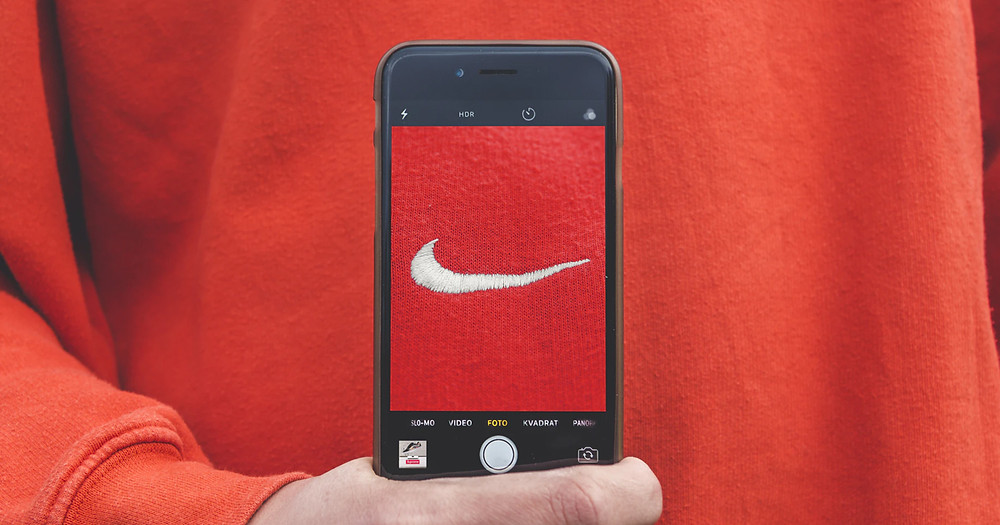 A person holding a smartphone with turned on camera and showcasing Nike logo