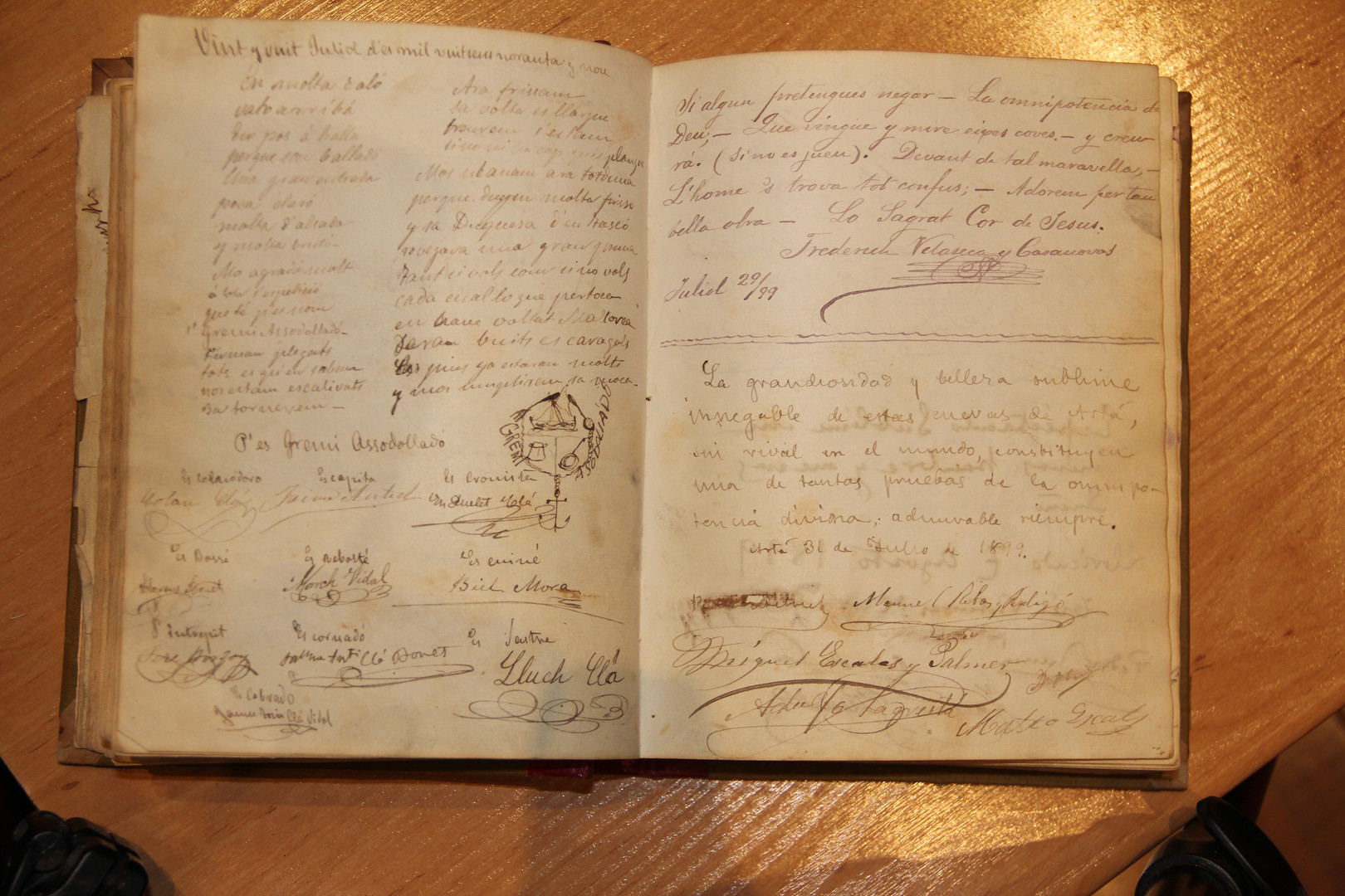"""On the left-hand page, glosa [a type of popular poetry] by the purser, Llorenç Bonet, and signatures of the rest of the expeditioners on the San Miguel in the volume of the Caves of Artà visitors' book corresponding to the period when they were visited by the expeditioners on the """"San Miguel"""" (courtesy of the Caves of Artà)."""