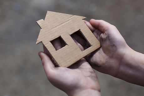 homeless boy holding a cardboard house,