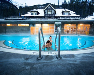 Man and woman stand in front of Banff Upper Hot Springs