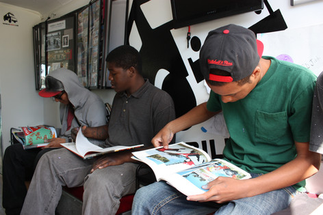 "Students	utilizing	the	interior	library	of	the	""Mobile	Mural	Lab"""