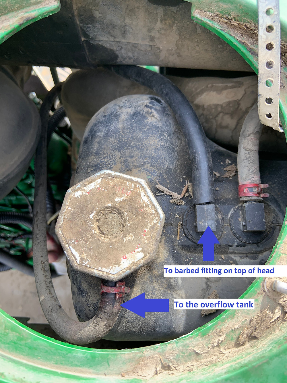 Small diameter coolant lines on John Deere 7810 tractor. The barbed fitting on top of the head appears to be for an air-bleed in the coolant system.