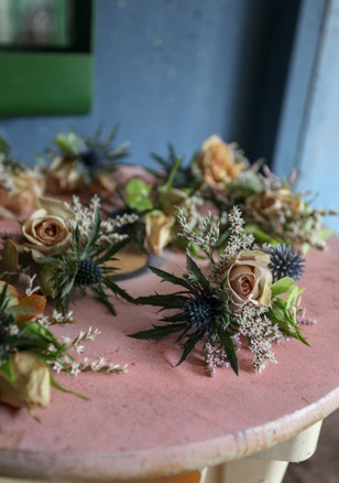 Buttonholes made with a mix of fresh and dried flowers