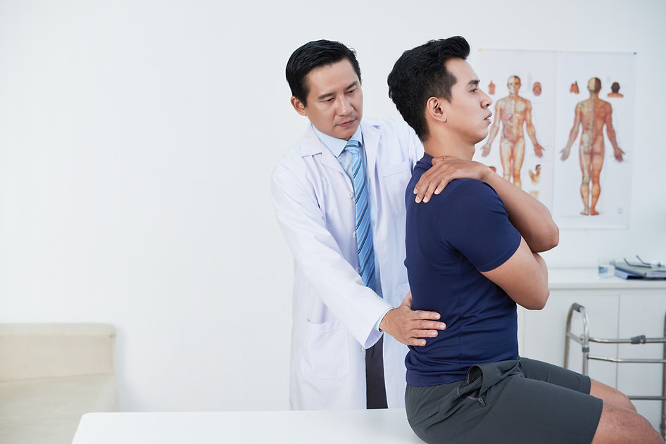 Mature osteopath palpating low back of patient in his office.jpg