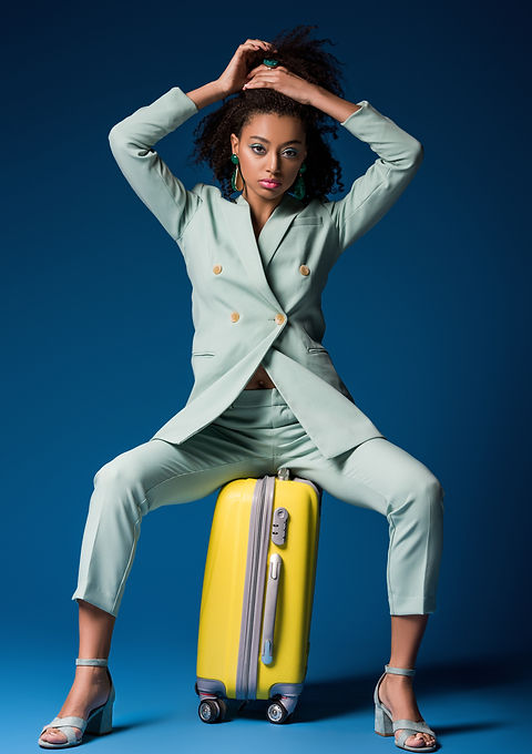 attractive african american woman sitting on travel bag on blue background.jpg