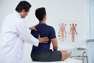 Doctor checking spine of a young man wit