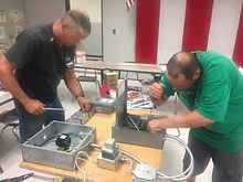 Two MSPMA membership working on electrical box at Summer Workshop