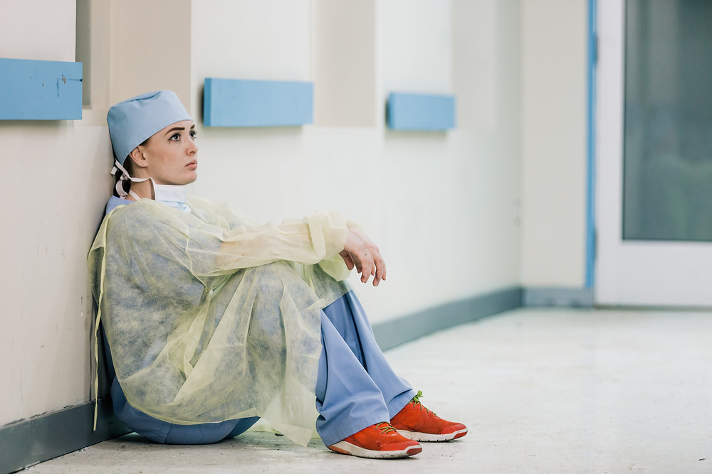 A tired doctor sits on the floor against a hospital wall