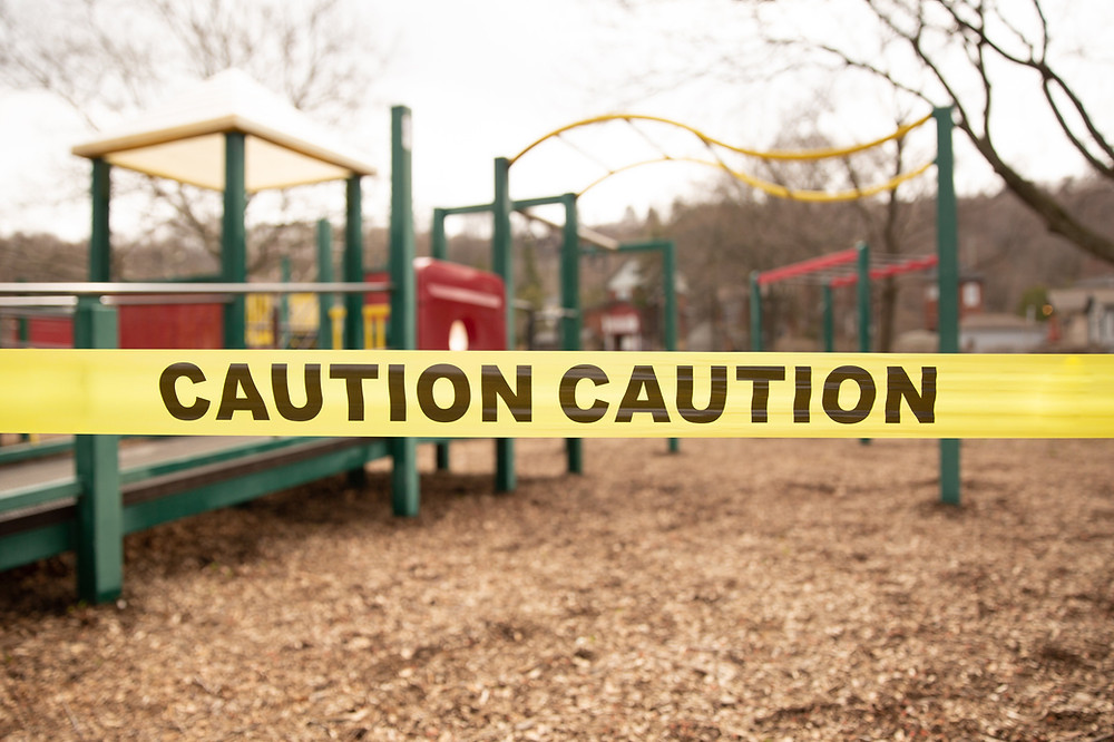 Caution tape is shown over top of a childrends playground