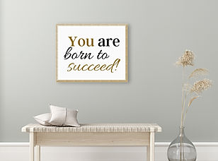 """tableau """"You are born to succeed!"""" accroché sur un mur au-dessus d'un banc d'intérieur."""