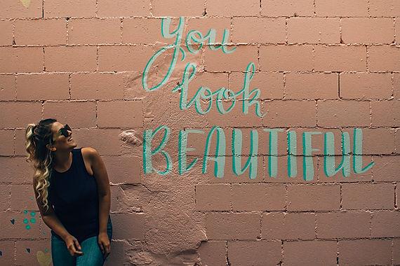 """femme qui regarde un mur avec l'inscription """"you look beautiful"""""""