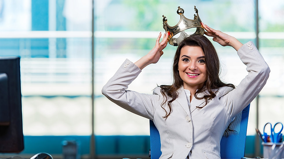 femme d'affaires assise derrière son bureau en train de mettre une couronne sur sa tête