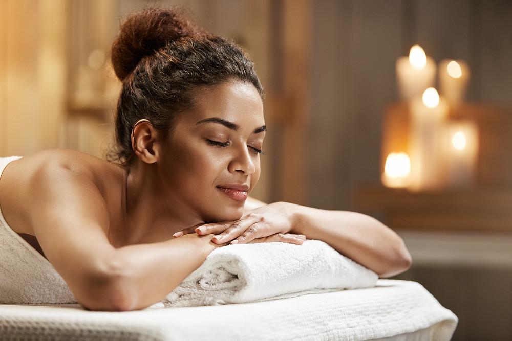 Femme paisiblement couchée sur une table de massage dans un décor très relaxant