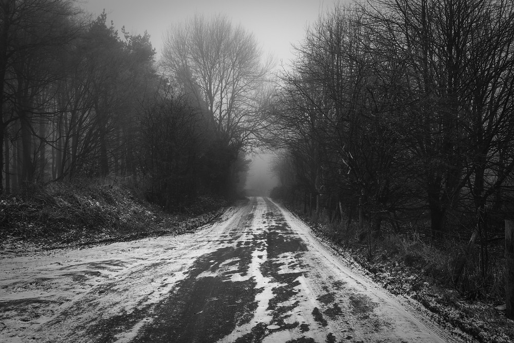 Black and white photograph of a Cotswold Country lane, snow, and mist.