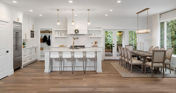 Beautiful panorama of white kitchen and dining room in new luxury home, with pendant light