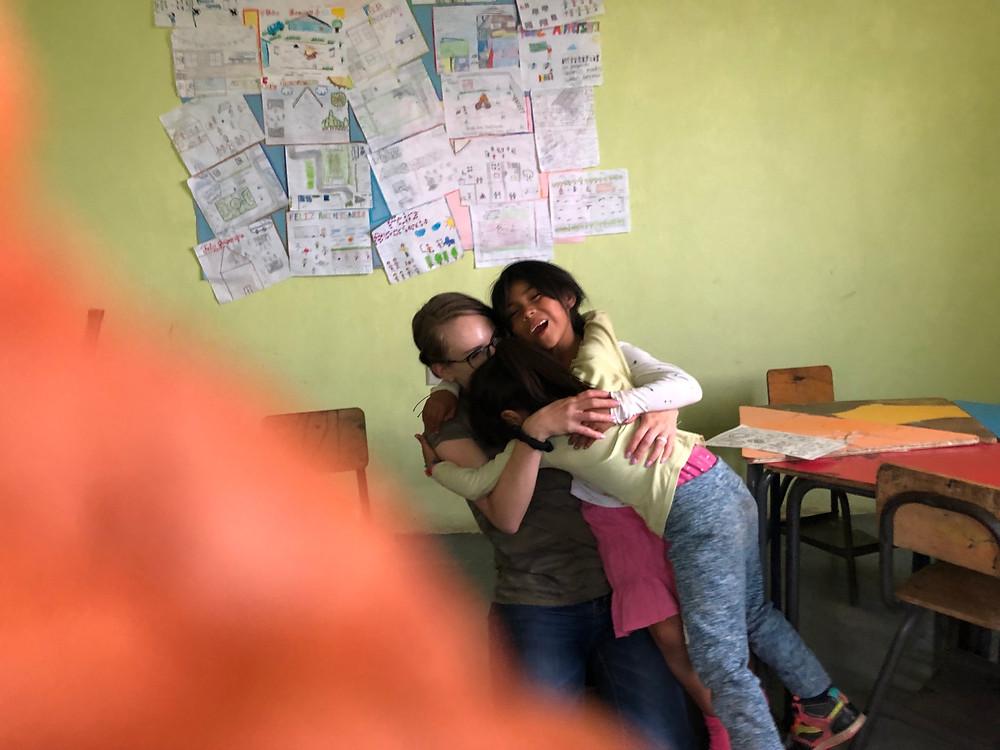 kids hugging teacher