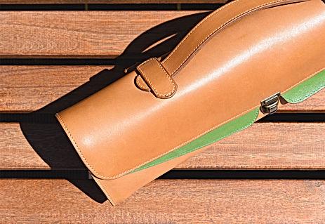 housse de flûte en cuir sur un banc en bois