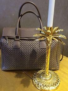 Braune Handtasche vor goldenem Kerzenständer