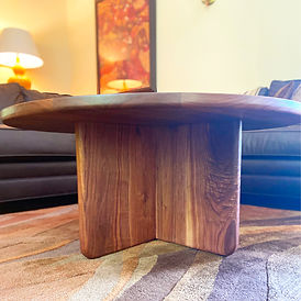 modern walnut coffee table with an x-base in a traditional living room framed by a brown leather couch and a batik on the wall