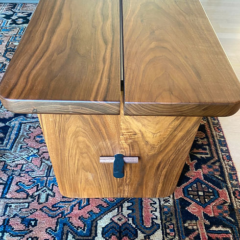 detail shot of a modern walnut dining bench with a black steel support