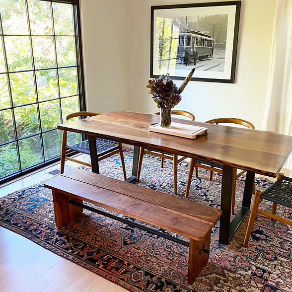 modern walnut dining bench paired with a live edge walnut dining table in a room with a turkish rug, wishbone chairs, floor to ceiling window and art