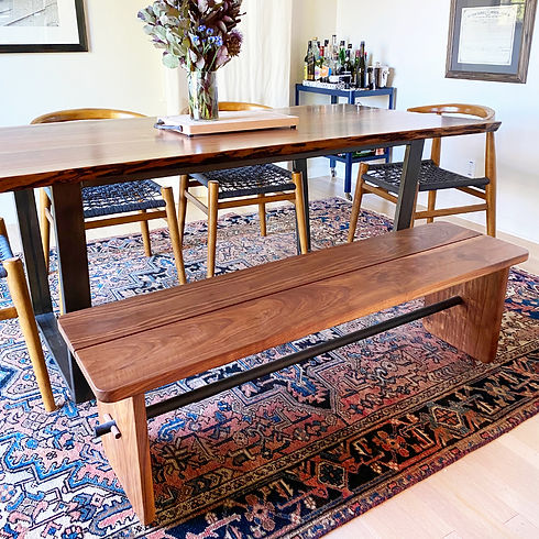 custom walnut bench with black steel base, dining room with kilim rug and wishbone chairs, bar cart, vase of flowers