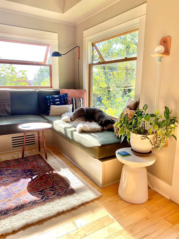 Modern loving room with a built in couch with green canvas duck cushions, large windows, modern lighting, a custom walnut accent table, plants in pots, a sheepskin rug, kilim pillows, and a chocolate labradoodle