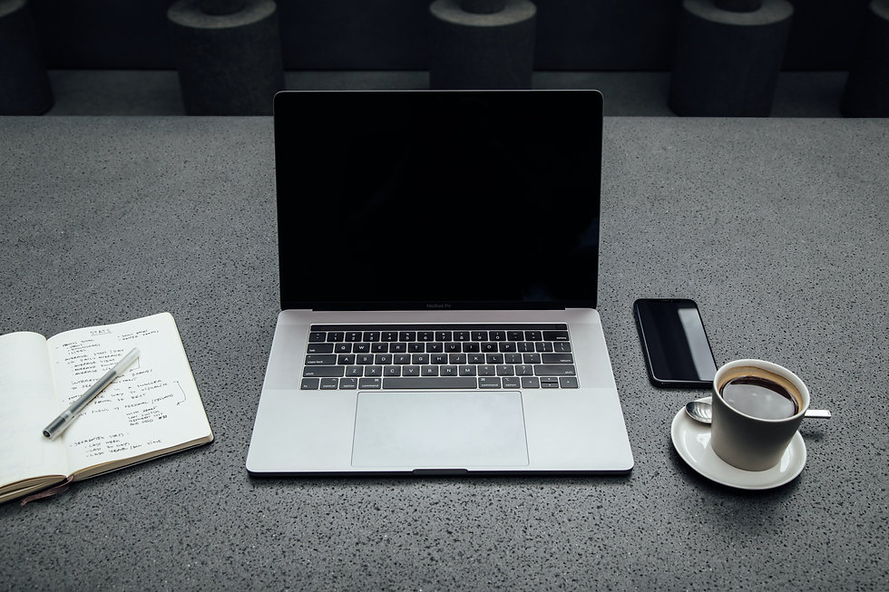 laptop on desk with notebook and mug of coffee