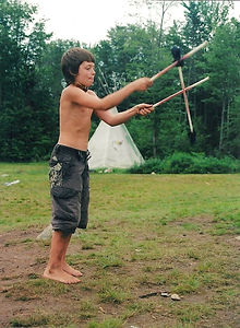 A boy plays with hand carved sticks
