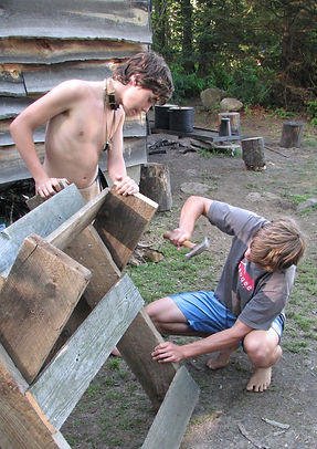 Two boys build a sawhorse at camp