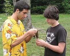 A summer camp counselor helps a camper fletch an atlatl dart