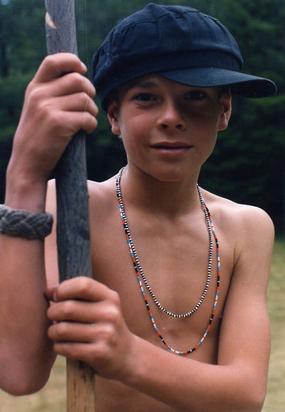 A camper wearing hand beaded necklaces leans on a carved walking stick
