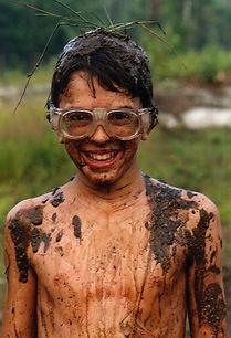 A muddy camper wearing goggles