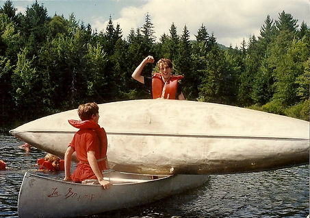 Campers recover a capsized canoe in a lake
