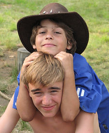 two campers pose while one of them wears a large hat