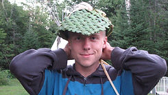 A summer camp counselor wears a hand woven reed hat