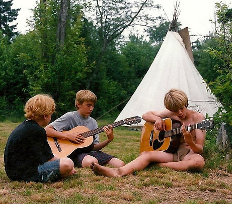 Two boys play guitar at camp with a tipi in the background
