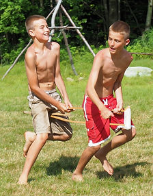 Two campers play with a crutch