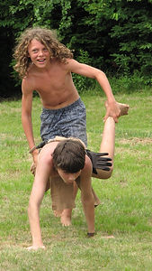 Two campers run a wheelbarrow race during field day