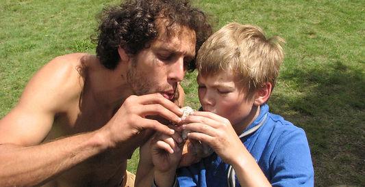 A summer camp counselor helps a camper start a birchbark fire