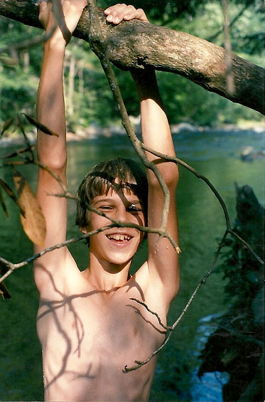 A boy hanging from a tree over water