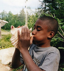 A camper uses a conch shell horn
