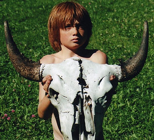 A boy lifts a bison skull during a cermony