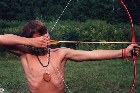 A boy draws a bow and takes aim
