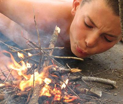 A boy starting a flint and steel campfire