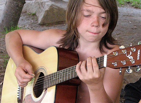 A boy playing acoustic guitar at summer camp