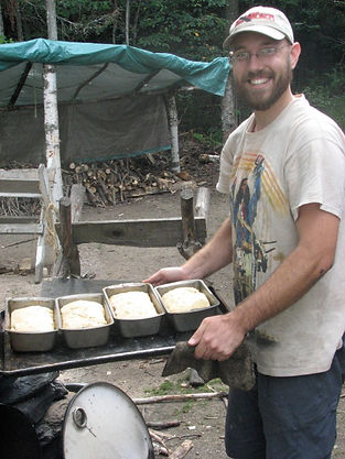 A camp counselor bakes bread in a brick oven