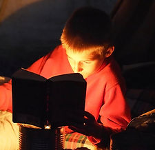 A boy reads a book by candlelight next to a campfire